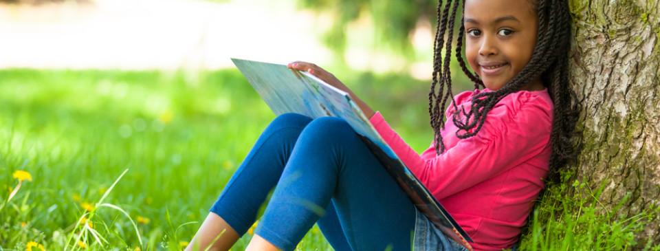 Girl sitting outside against tree, reading