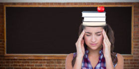 Woman with books on head rubbing temples in front of chalkboard